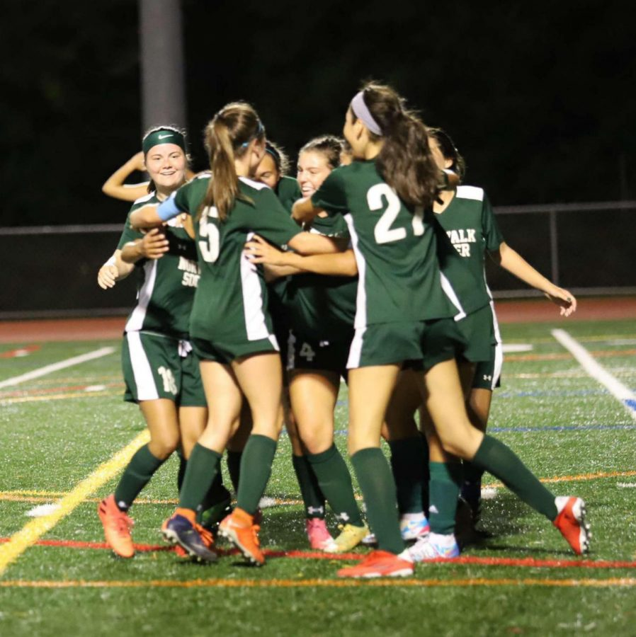 NHS Girls Soccer Team in a huddle.